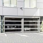 dvoje průmyslová garážová vrata prosklená, za sklem jsou vidět zaparkované vozy v garáži