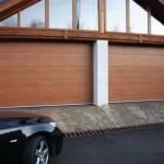 dům se dvěmi garážovými vraty v barvě zlatý dub a před nimi vůz