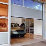 pootevřená průmyslová vrata s prosklením a uvnitř budovy auto