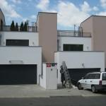 zástavba řadových domů s garážovými vraty, auto před garáží